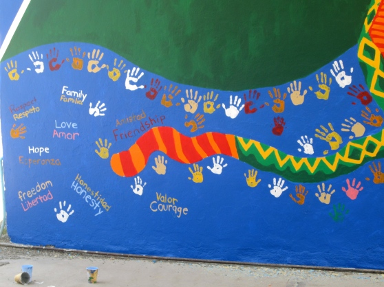 We made a lasting impression by painting our hands and putting our hand prints on the mural. We also painted words, representing values we find important for the kids.